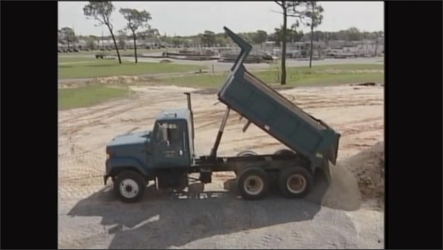 2000s: Man operates dump truck, lifts bed, dumps load of gravel.