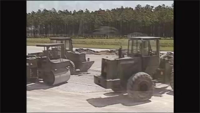 2000s: Men drive construction equipment. Man scoops dirt with bucket.