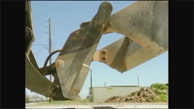 2000s: Front segment of front loader bucket opens up, rear segment rests on the ground.
