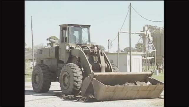 2000s: Man operates front end loader, scoops dirt into bucket.