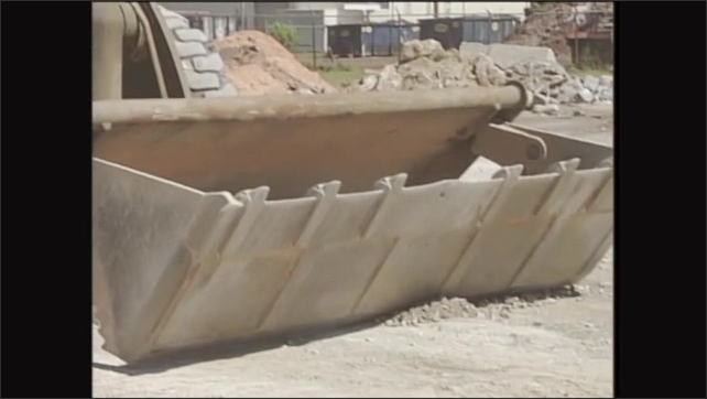 2000s: Man operates front end loader, scoops dirt into bucket, reverses aways from pile.