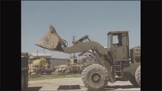 2000s: Man operates front end loader, dumps dirt into dump truck, reverses away from dump truck.