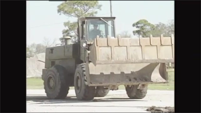 2000s: Front end loader dumps dirt onto pile. Man operates front end loader.