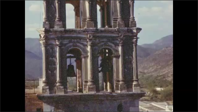 1950s: View of town with mountains in background. Close-up of church bell tower. Low building with series of arches and cows standing in front of it.