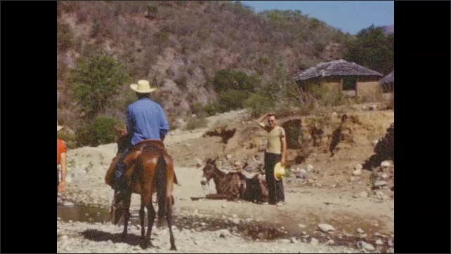 1950s: Three people on mules ride down rocky path. Person sitting on mule talks to person standing next to mule lying down. Man forces mule to stand up.