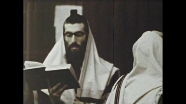 1970s: Hand flips through pages of prayer book on altar. Men sway and speak in prayer. Man stands near lighted altar and speaks from Torah.