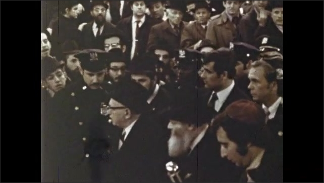 1970s: Men crowd around sidewalk leading to synagogue. Police and barricades protect sidewalk to synagogue. Police lead men in suits into synagogue. Crowds of Jewish men stand in temple.