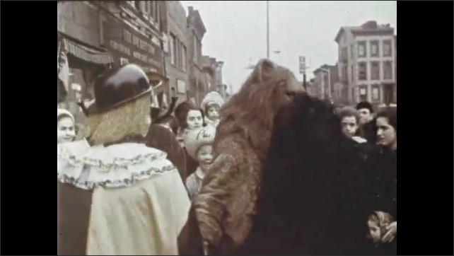 1970s: Children stomp and use noisemakers in synagogue. People in costume dance in circle. Children in costume walk through city streets.