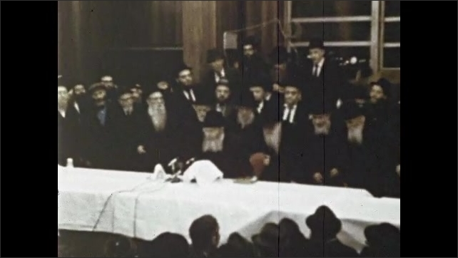 1970s: Jewish men crowd around table in synagogue. Rabbi sits at table in crowd of men. Rabbi speaks into microphone to crowd of adherents in temple.