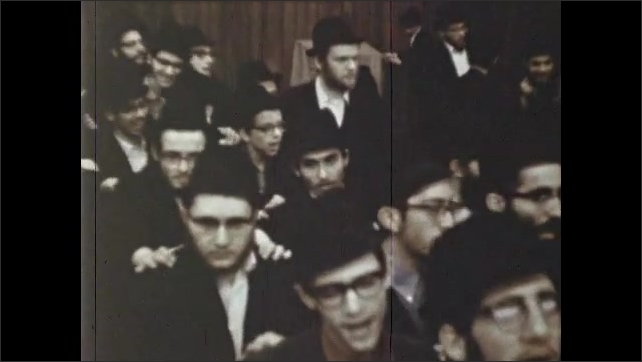 1970s: Rabbi claps hands and congregation sings. Jewish men dance and sing in synagogue. Men clap and dance in synagogue.