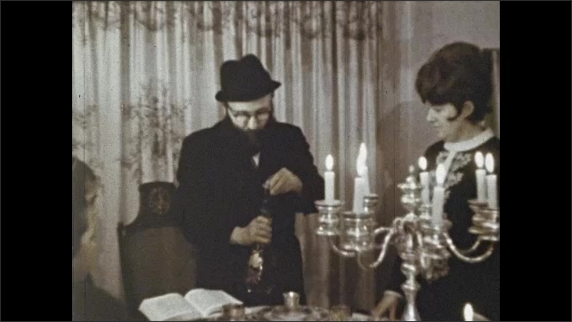 1970s: Woman lights candle on dining table. Women and girls stand around candelabra on table in dining room. Man pours wine into small chalices on silver plate.