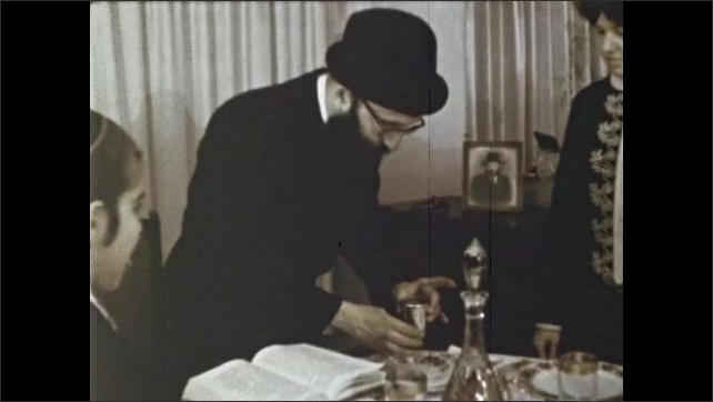 1970s: Man holds chalice of wine and looks at Torah. Man sits at table and drinks from chalice. Man pours wine from chalice into small glasses. Torah on table.