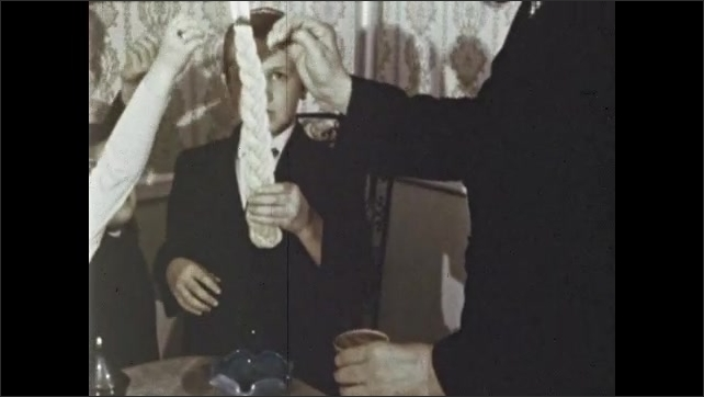 1970s: Family passes chalice. Man holds glass of wine. Boy holds large braided candle. Man and family move hands around candle. Man sits and drinks from wine glass.