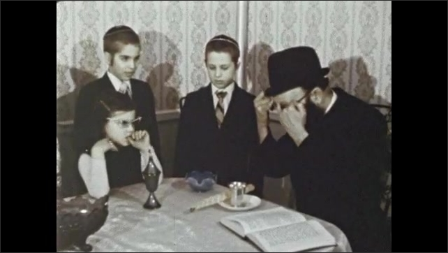 1970s: Man pours wine into bowl and extinguishes candle in it. Man and children dip pinkies into wine bowl and draw fingers across eyebrows. Men walk together in crowd at Jewish wedding.