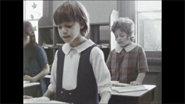 1970s: Classroom, children stand at desks, recite from books, sing, sway. Children play on playground, hold hands, dance in circle.