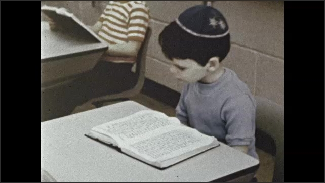 1970s: Classroom, boys sit at tables, lean forward on books, follow Hebrew text with finger. Boys sit at desks, recite prayers, rock back and forth. Boy writes on chalkboard, teacher watches.