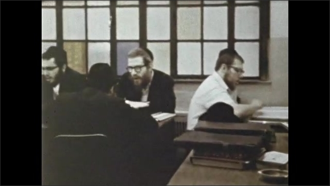 1970s: School, men sit at table, read from large books, follow text with fingers, talk, discuss, gesture.