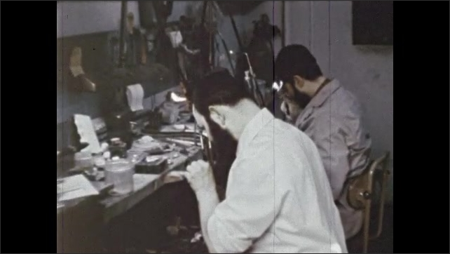 1970s: Men work with machinery, use tools, man examines paper, folds it, holds it up. Jeweler sits at work bench, saws small object. Man follows text with finger in large book.
