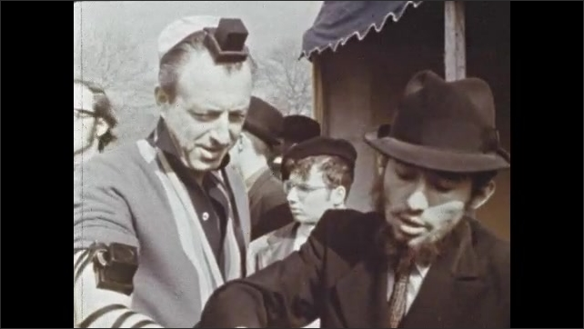 1970s: Man helps other man put on tefillin, yarmulke, winds leather strap around man's fingers. Men talk.