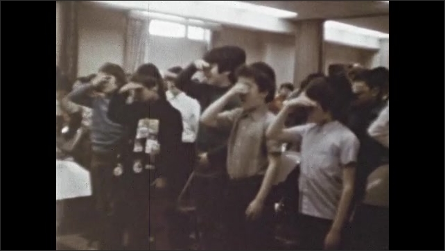 1970s: Large room full of children. Boys stand, shield eyes with hands, uncover eyes. Girls sit, recite in unison.