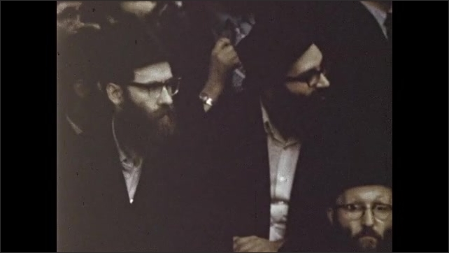 1970s: Crowded room full of men and boys, rabbi walks up to stage with large menorah.