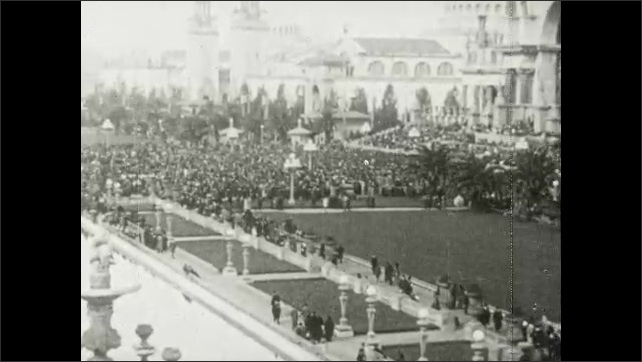 1910s: Crowds of people outside World's Fair. Intertitle card. Columns.