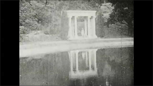 1910s: Woman walks around columns, walks down to water's edge.