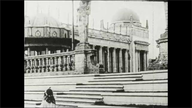 1910s: Woman stands on balcony. Woman runs through World's Fair buildings.