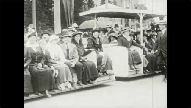 1910s: People walk, ride train, ride in cart. People watch airplane fly in sky.