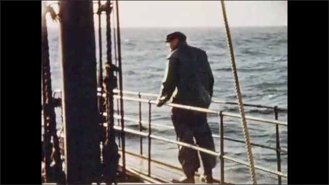 1950s: DURBAN, SOUTH AFRICA: man stands on bridge . Waves around ship. Speed dial on boat. Man stands by loaded gun
