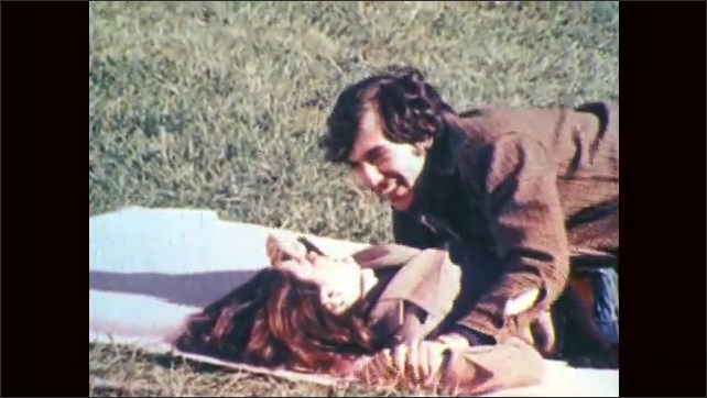 1970s: A couple tickles each other, they play around on blanket in the grass. Man holds woman