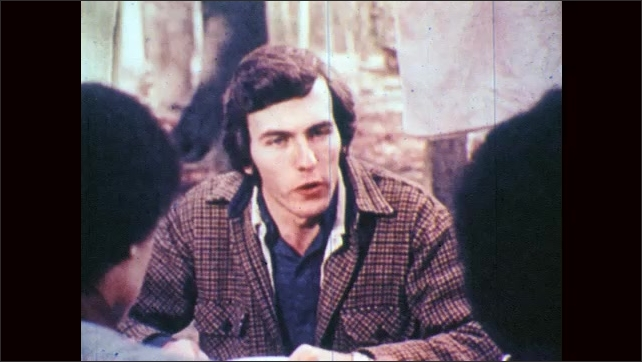 1970s: Two couples sit and talk at picnic table in the woods and have food, tent in background. Face of man who sits and talks seriously.