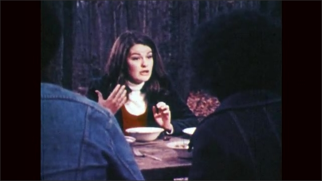 1970s: Man eats, talks and looks upset. Woman talks to couple and gesticulates. Man talks.