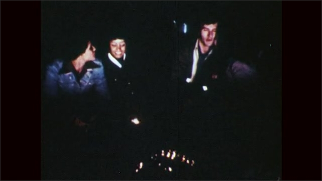 1970s: People toast marshmallows over campfire.  Woman kisses man.  People talk.