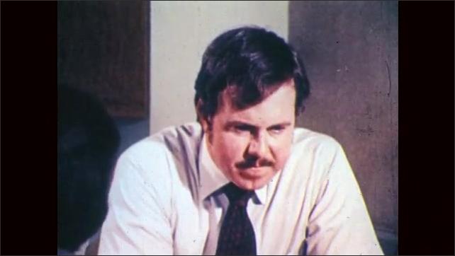 1970s: Office.  Men speak.  Man shakes head.
