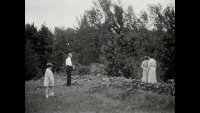 1930s: Man plays with little girl in white dress on lawn; family members harvest melons from vegetable garden.