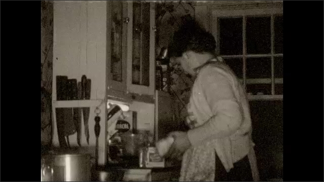 1950s: Woman tends to cooking in kitchen as cat look on.