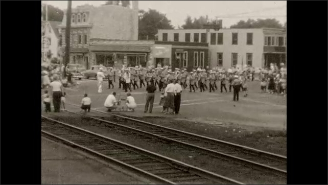 1950s: Marching band, groups of citizens march in small town parade.