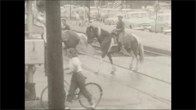 1950s: Men on horseback, children on bicycles parade across railroad tracks in small town.
