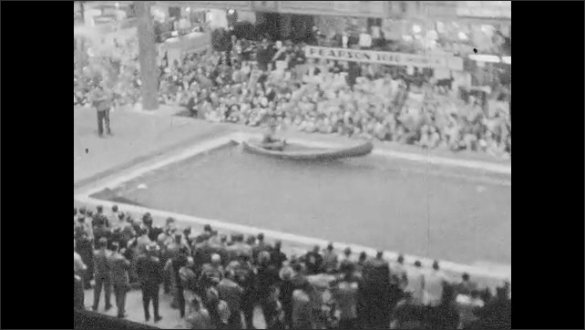 1950s: Acrobats perform for large convention audience; man paddles canoe across indoor pool in convention hall.