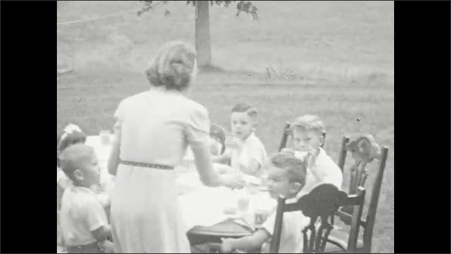 1950's: Lambs frolic on porch of farm house; mother presents cake to table full of children at outdoor table.