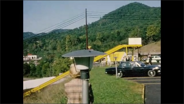 1960s: Man crosses parking lot adjacent to large yellow slide.