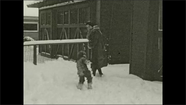 1930's: Mother and two children play in snow outside house.