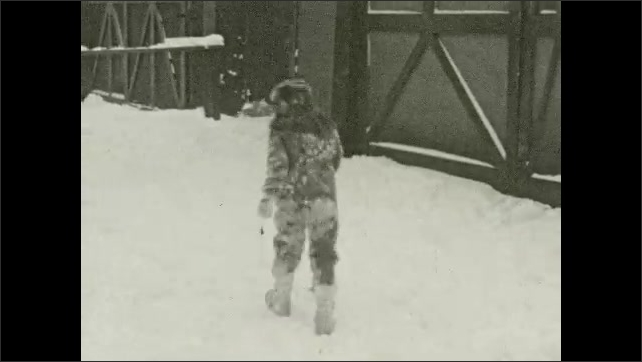 1930's: Mother and two children play in snow in suburban yard.