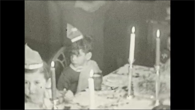 1930's: Small children sit around table at birthday party.