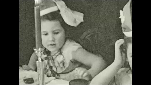 1930's: Small girl at party blows out candles on birthday cake.