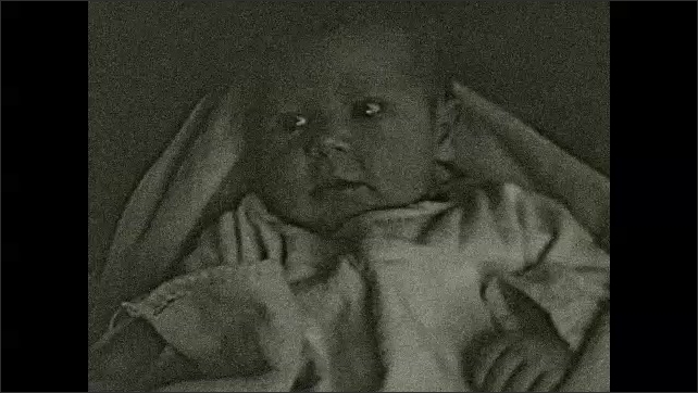 1930's: Mother cradles newborn baby in arms; Small girl holds baby's hand on sofa.