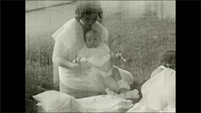 1930's: Mother tends to baby on lawn blanket.