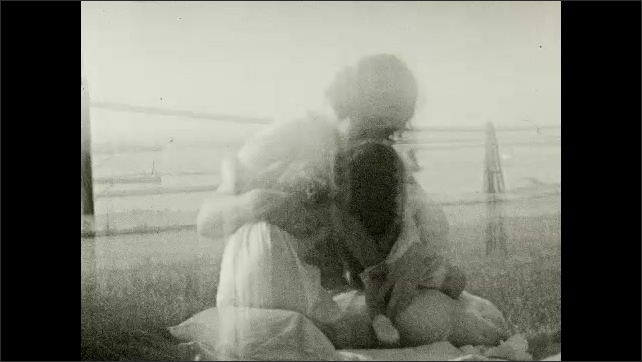 1930's: Mother tends to baby, small girl on lawn blanket.