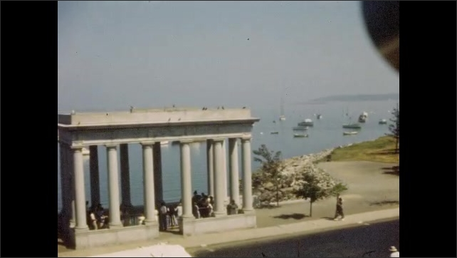 1940s: Boats moored in Plymouth Harbor by Plymouth Rock memorial; statue of American Indian Massasoit.